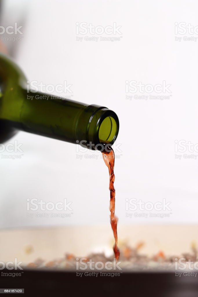 Pouring red wine into skillet. Making Lasagna Bolognese Series. stock photo