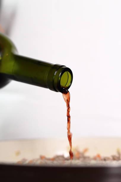 rotwein in die pfanne gießen. herstellung von lasagne bolognese serie. - weinsoße stock-fotos und bilder