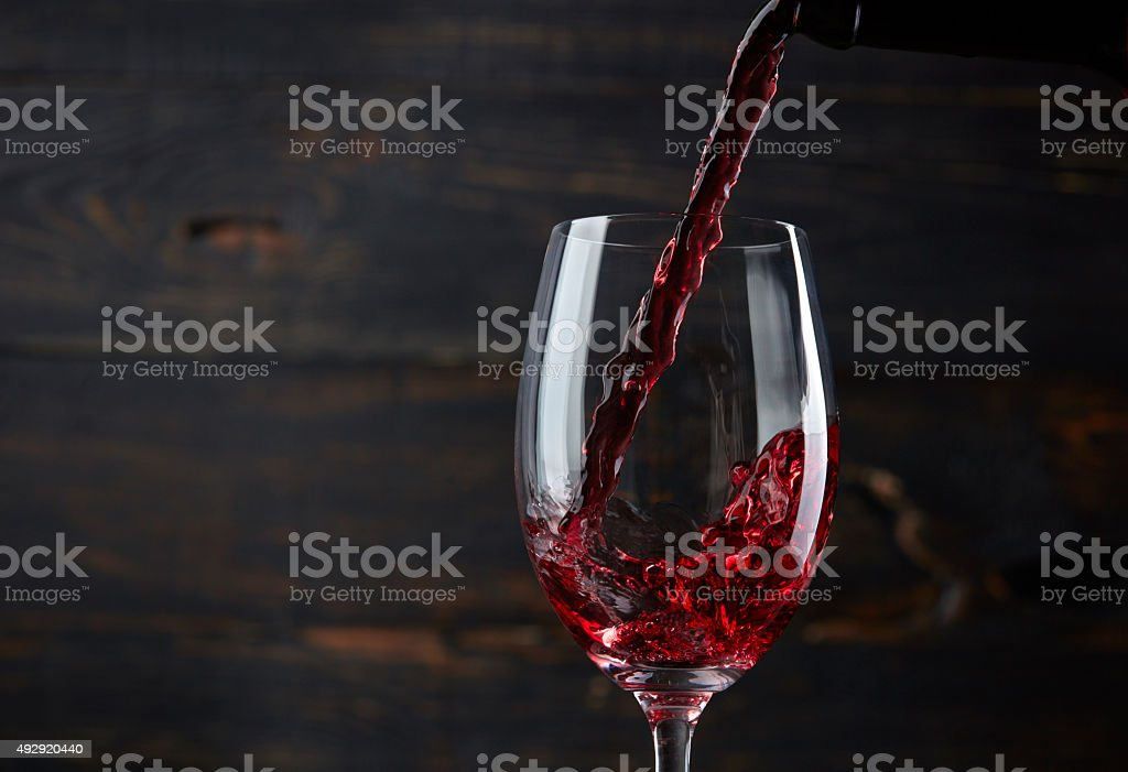 Pouring red wine into the glass against dark wooden background stock photo