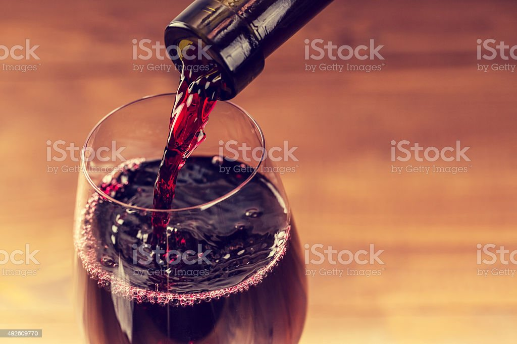 Pouring red wine into the glass against wooden background stock photo