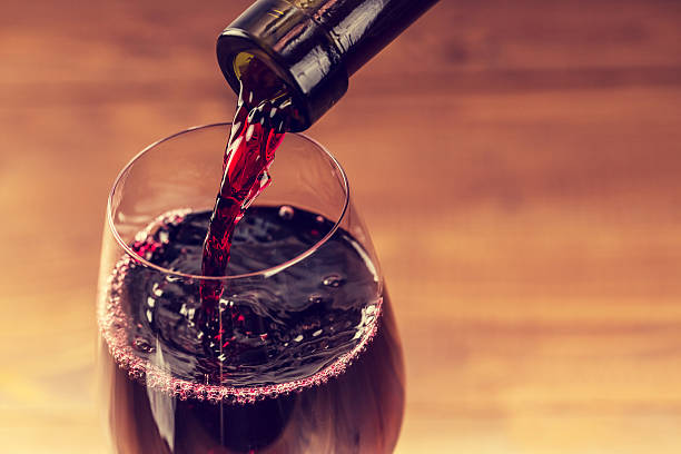 pouring red wine into the glass against wooden background - wine glass stock photos and pictures