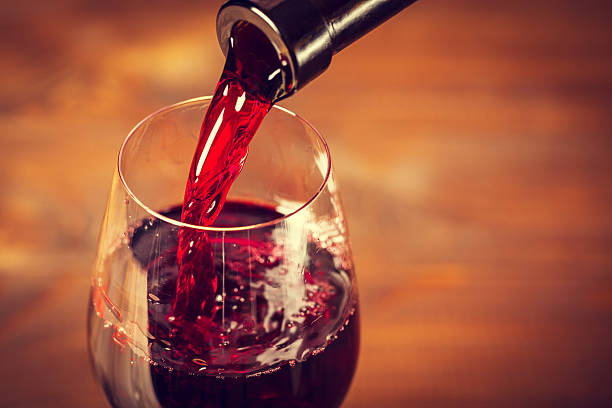 Pouring red wine into the glass against wooden background Pouring red wine into the glass against wooden background merlot grape stock pictures, royalty-free photos & images