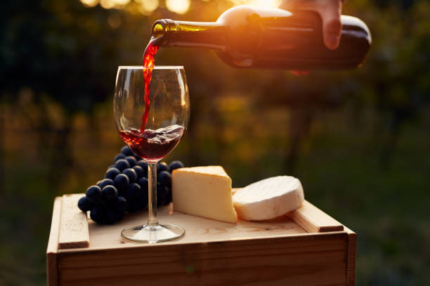 Pouring red wine into the glass in the vineyard Pouring red wine into the glass in the vineyard at sunset cabernet sauvignon grape stock pictures, royalty-free photos & images