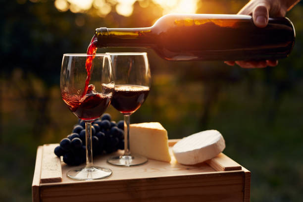 Pouring red wine into the glass in the vineyard Pouring red wine into the glass in the vineyard at sunset cheese stock pictures, royalty-free photos & images