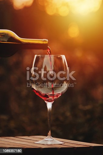 istock Pouring red wine into the glass. Pour red wine. 1089357180