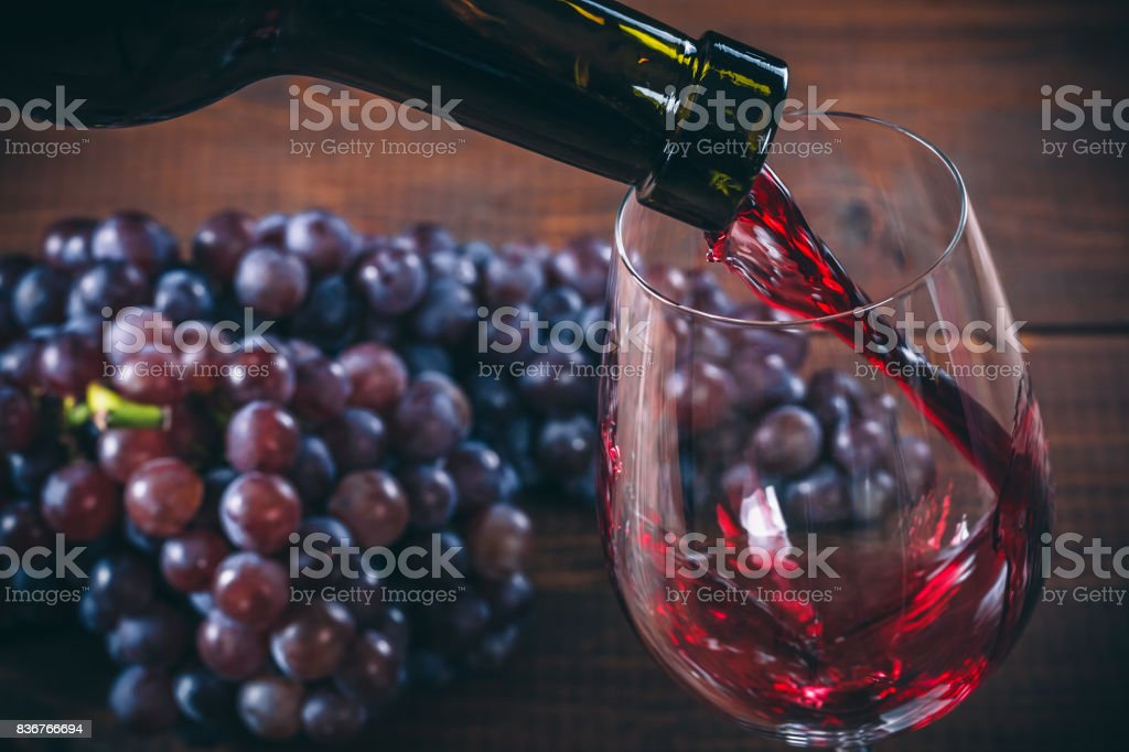 Pouring red wine into the glass with a bunch of red grapes against wooden background Pouring red wine into the glass with a bunch of red grapes against wooden background Alcohol - Drink Stock Photo