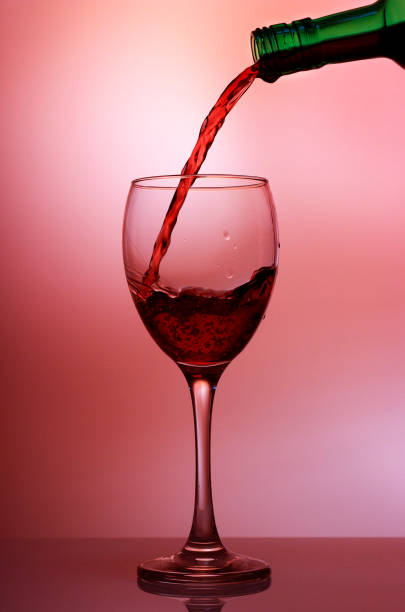 Pouring red wine into the wineglass close-up, isolated on pink gradient background stock photo