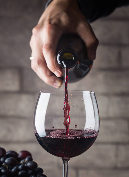 Pouring red wine Pouring red wine into the glass against wooden background merlot grape stock pictures, royalty-free photos & images