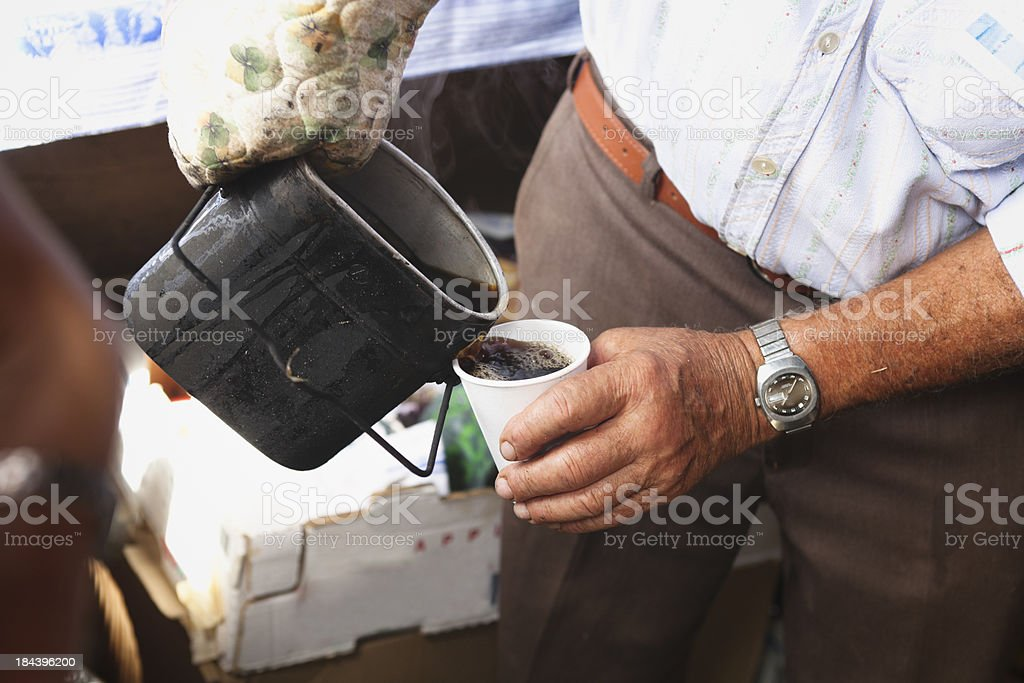 Pouring schnapps coffee from a Swiss Army gamelle royalty-free stock photo