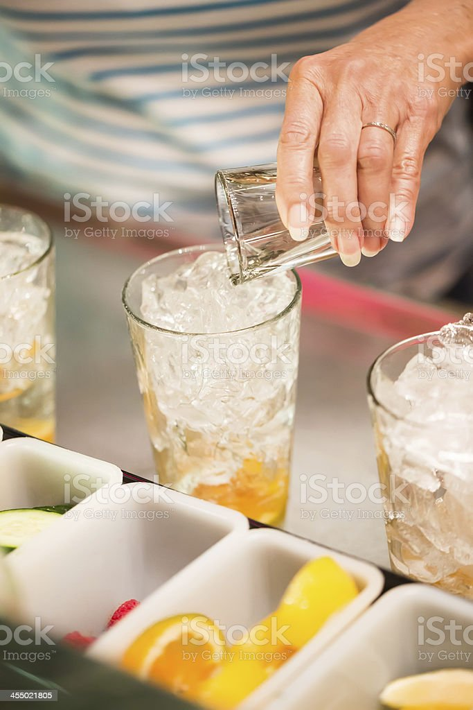 Pouring shot of alcohol into a glass with ice royalty-free stock photo