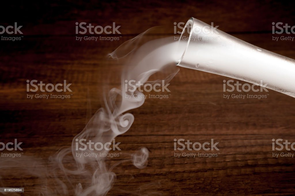 Pouring smoke from putting dry ice in the water, in transparent vest, on wooden background, dark and mysterious style stock photo