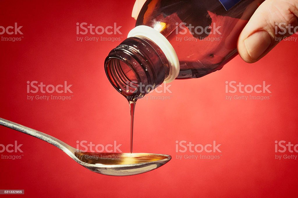 Pouring some cough syrup stock photo