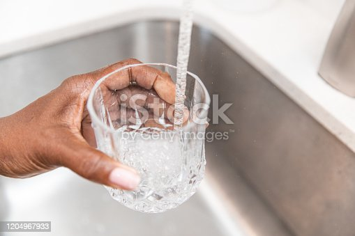 Unrecognizable woman pouring herself a glass of tap water from the kitchen sink