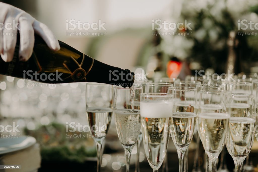 Pouring sparkling white wine from bottle into the wine glass.