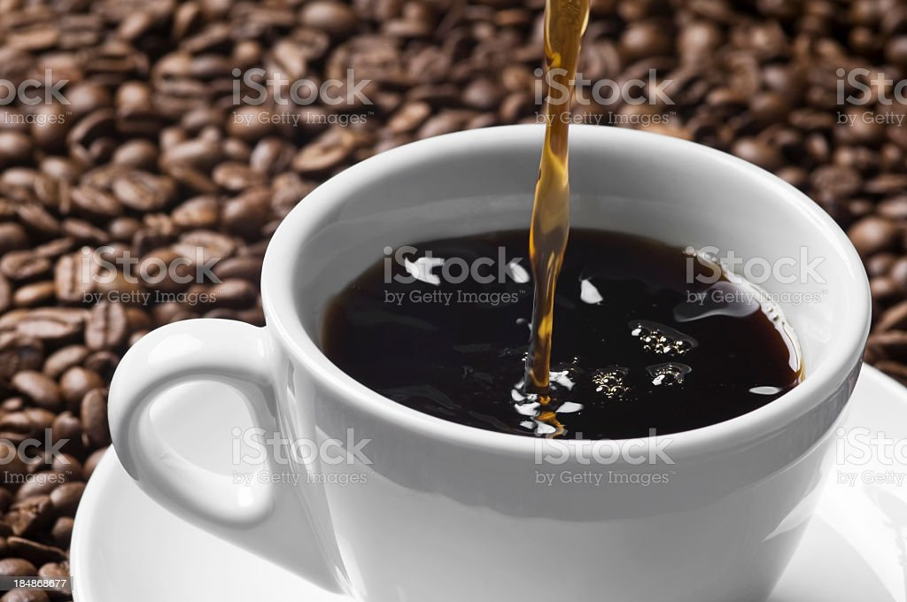 Pouring stream of brown coffee to white cup royalty-free stock photo