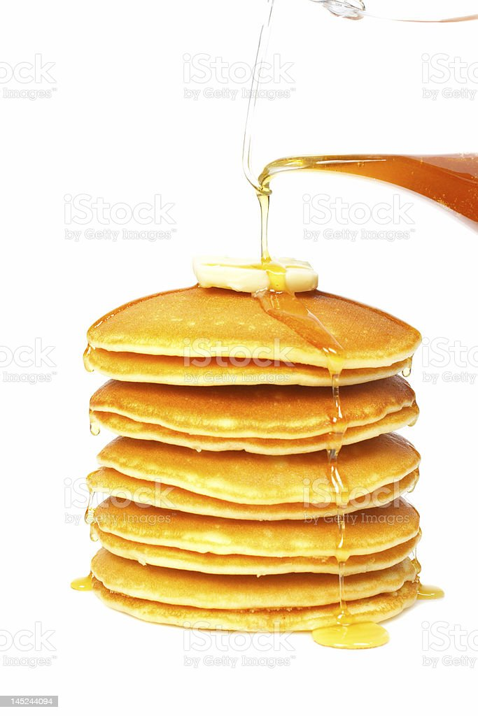 Pouring syrup on the pancakes stock photo