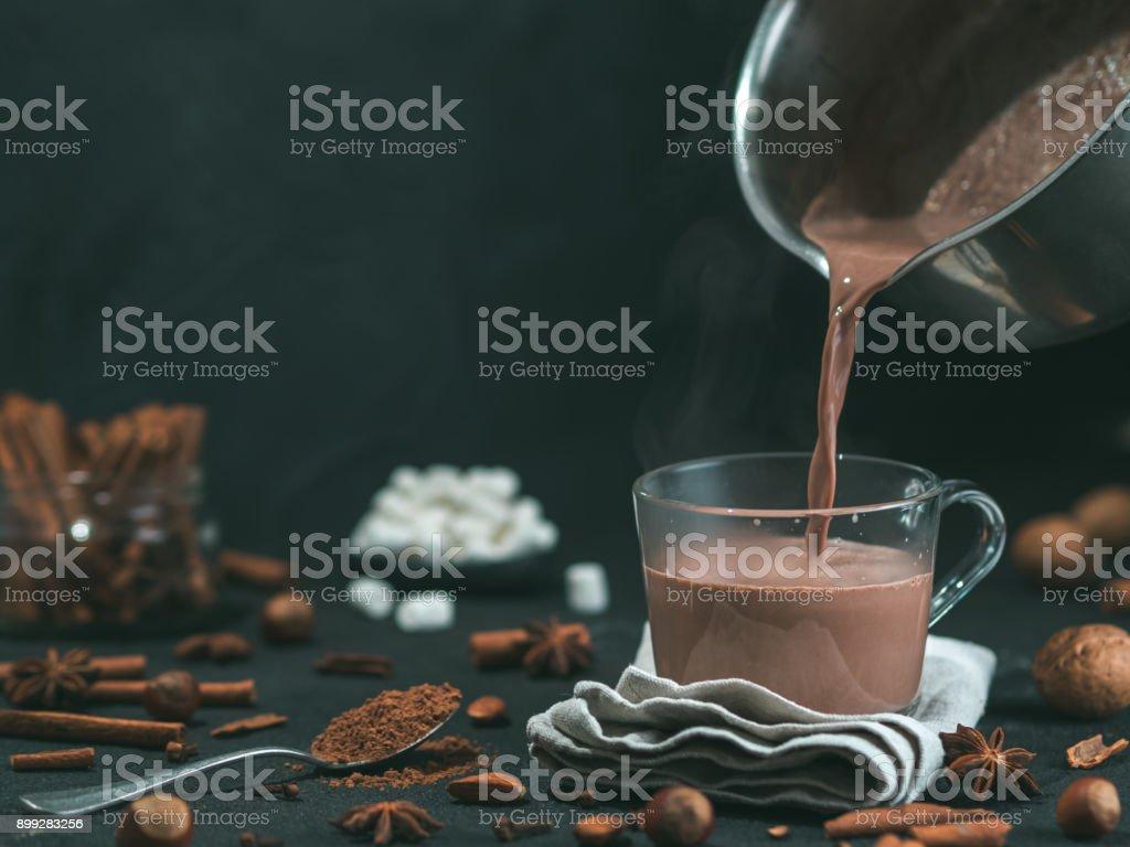 Despejando saborosa bebida de cacau a caneca na mesa - foto de acervo