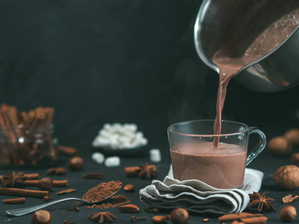 pouring tasty cocoa drink into mug on table - hot chocolate stock photos and pictures