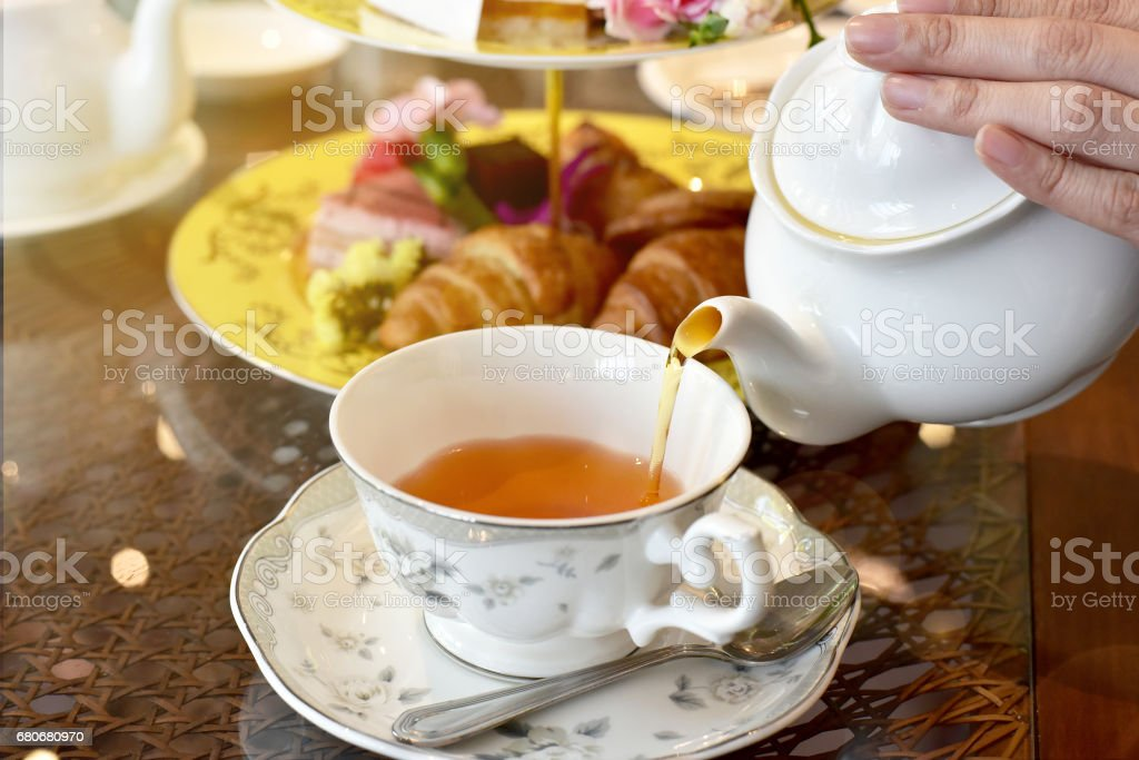 Pouring tea from vintage teapot to the cup, English Tea Time. stock photo