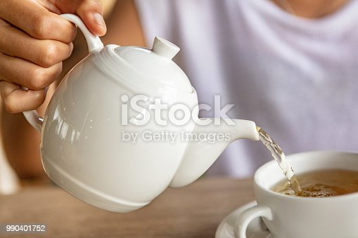 Close-up of woman pouring hot water in tea cup