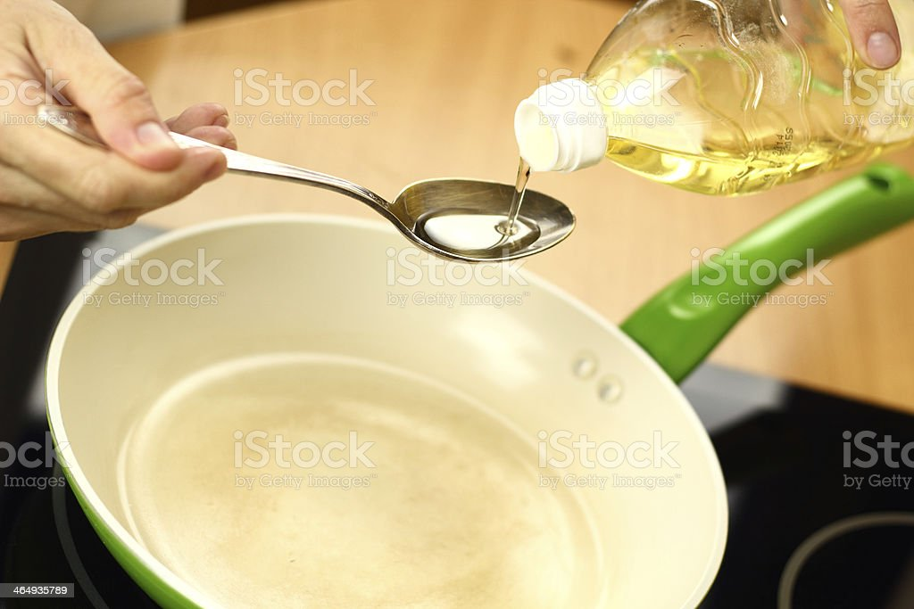 Pouring vegetable oil into frying pan stock photo