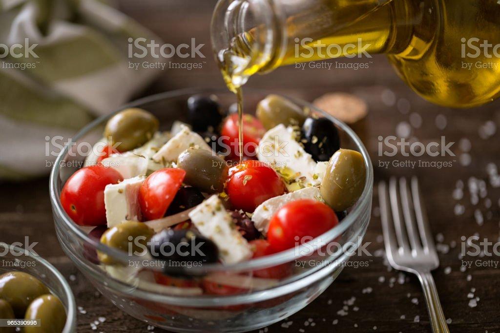 pouring virgin olive oil on vegetarian salad with fresh vegetables, feta and green olives zbiór zdjęć royalty-free