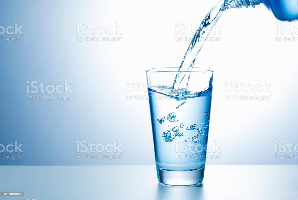 Gießen Wasser aus der Flasche in Glas Lizenzfreies stock-foto