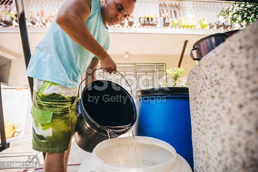 Young man is filling a barrel with water from a bucket