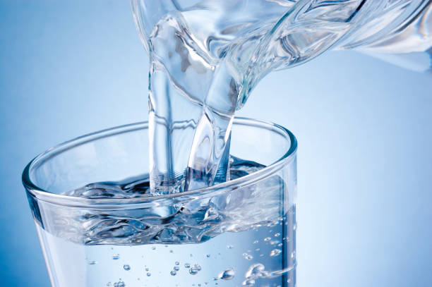 在藍色背景下將水罐中的水倒進玻璃 - 水 個照片及圖片檔