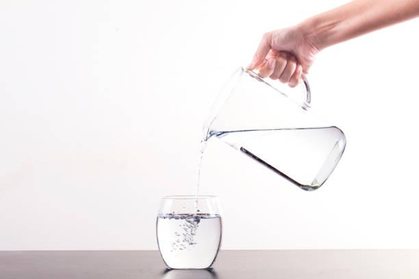 Pouring Water From Pitcher Into Glass, isoliert auf weißem Hintergrund mit Kopierraum – Foto