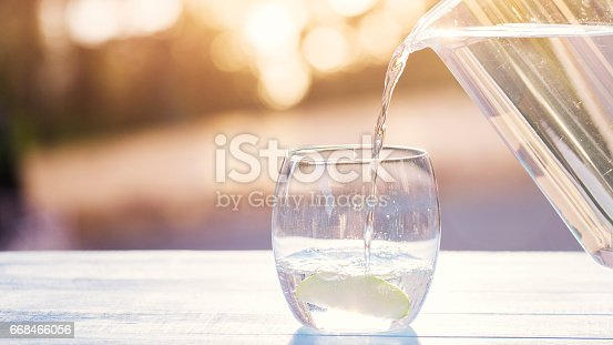 Hand Pouring Water From Pitcher Into Glass