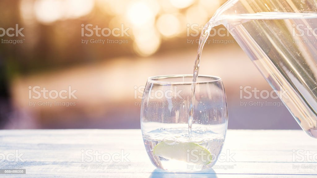 Pouring Water From Pitcher Into Glass - foto stock