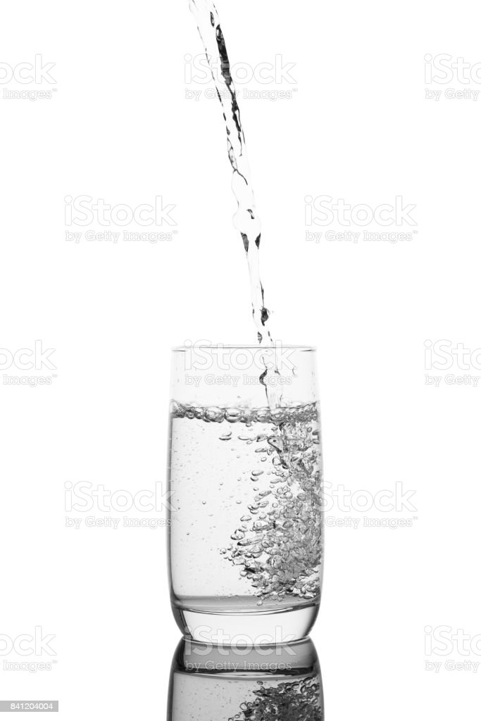 Pouring water in a glass, isolated on a white background stock photo