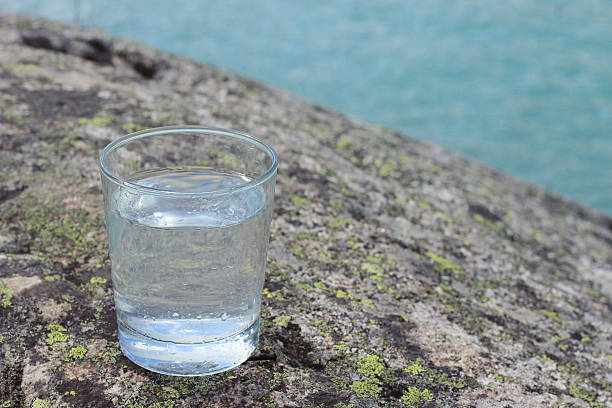 Pouring water into a glass against the nature background. stock photo