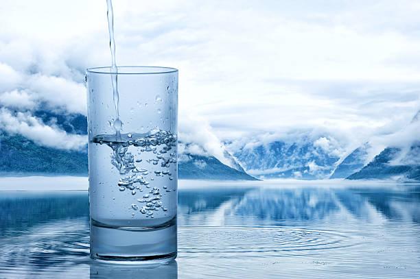 pouring water into a glass against the nature landscape - wasser trinken abnehmen stock-fotos und bilder