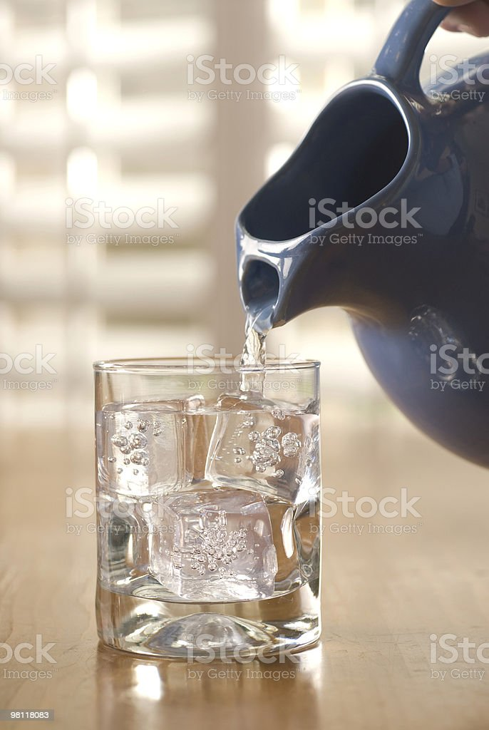 pouring water into a glass of ice stock photo