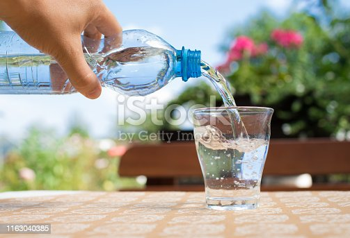 Woman's hand pouring mineral water into a glass.