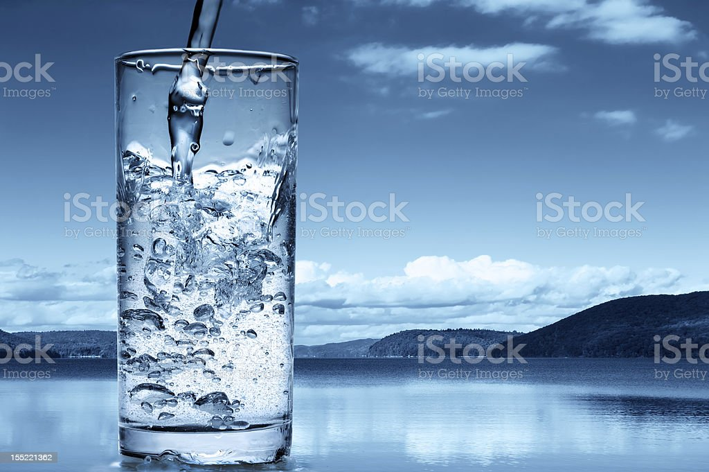Pouring water into a glass stock photo