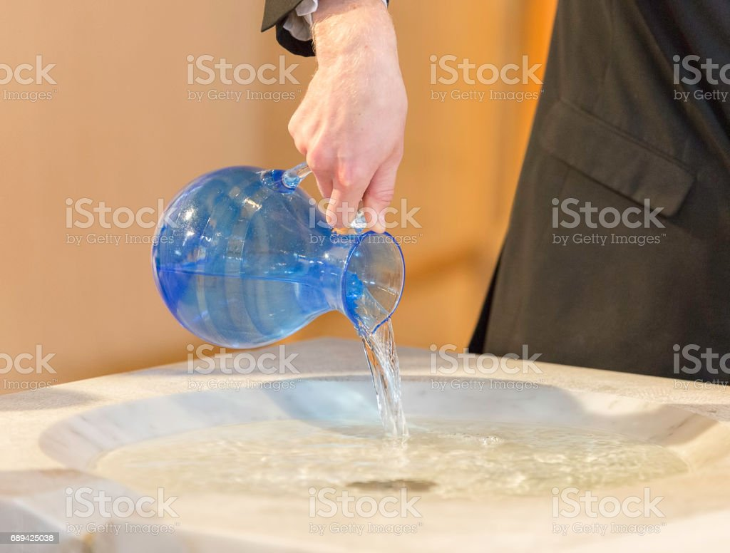 Pouring Water into Baptismal Font stock photo