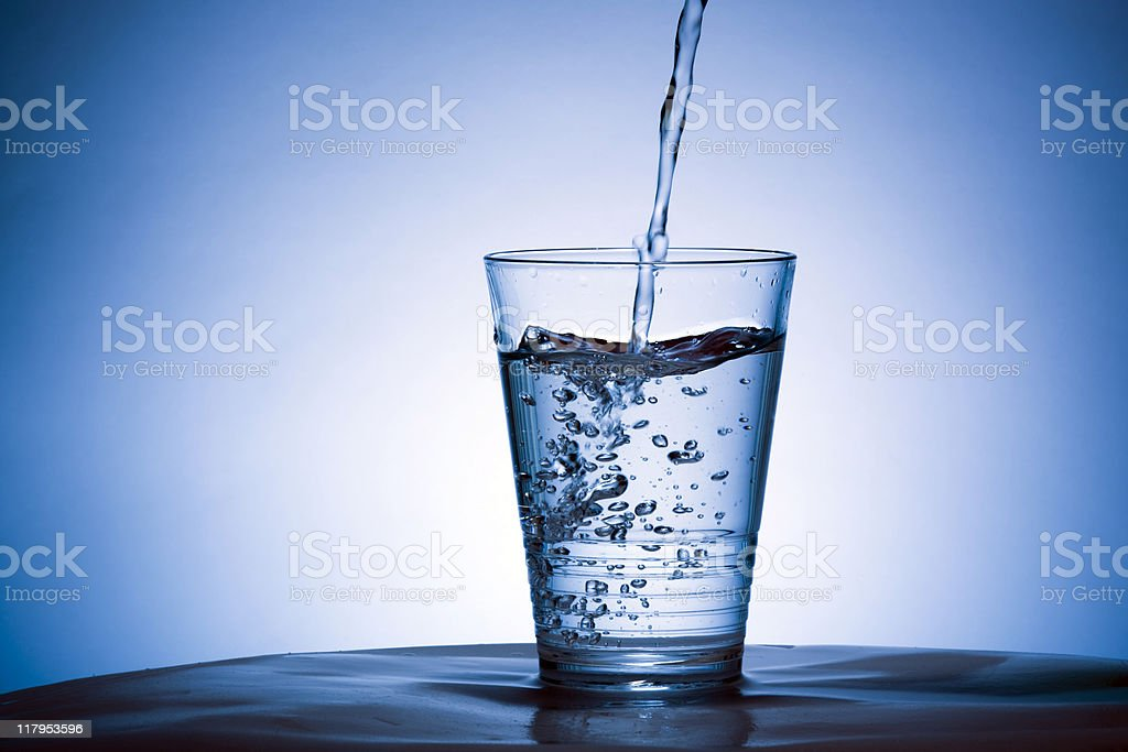 Pouring water into glass Cold water being poured into a glass. Abstract Stock Photo