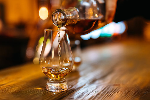 Pouring whiskey in glass on bar counter.