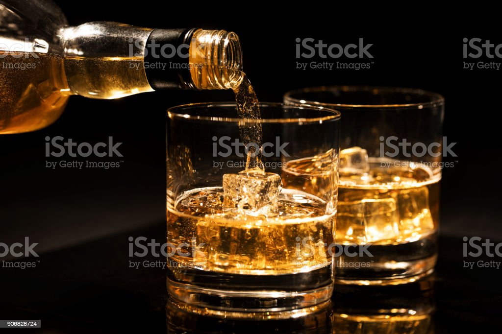 pouring whiskey into a glass with ice cubes on black background stock photo