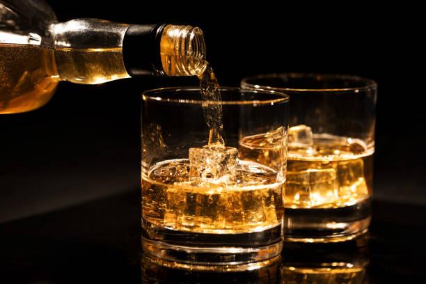 whisky in ein glas mit eiswürfeln auf schwarzem hintergrund gießen - goldene bar stock-fotos und bilder