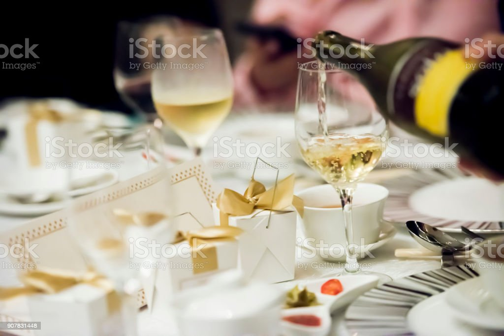 Pouring white wine in the glass stock photo