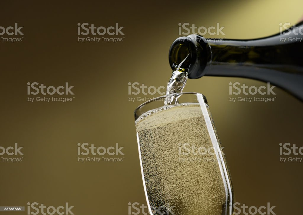 Pouring white wine into a wineglass stock photo