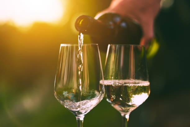 Verter el vino blanco en vasos - foto de stock