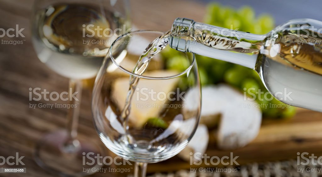 Pouring white wine into the glass against wooden background stock photo