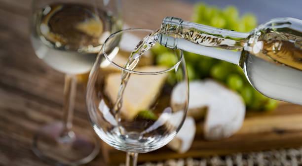 despejando o vidro contra o fundo de madeira com vinho branco - fine dining - fotografias e filmes do acervo