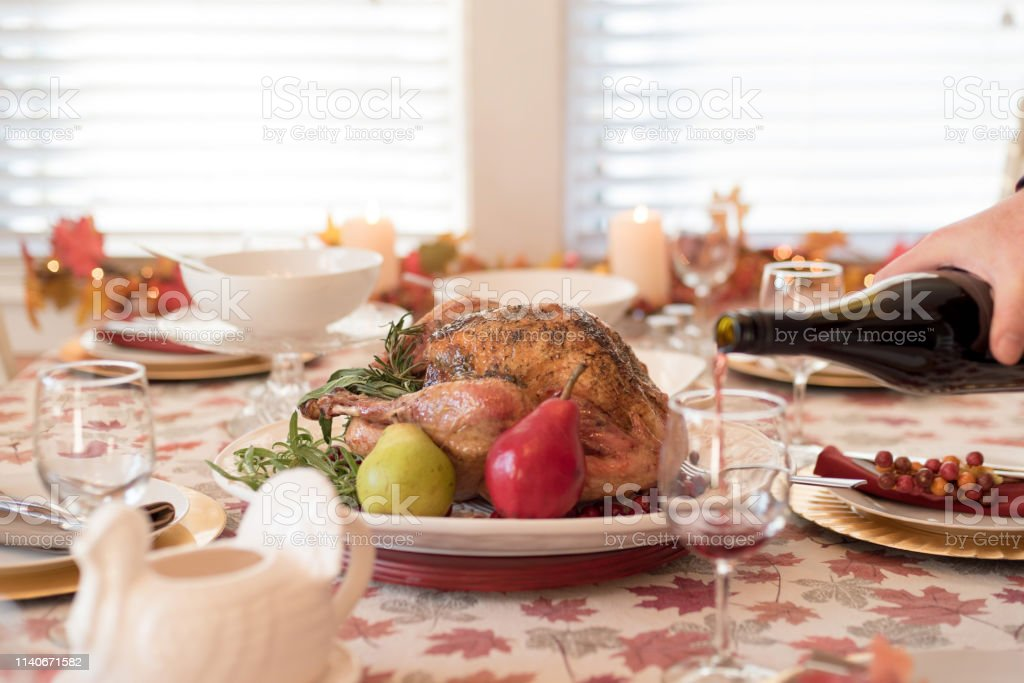 Holiday dinner table with roasted turkey, man pouring red wine in...