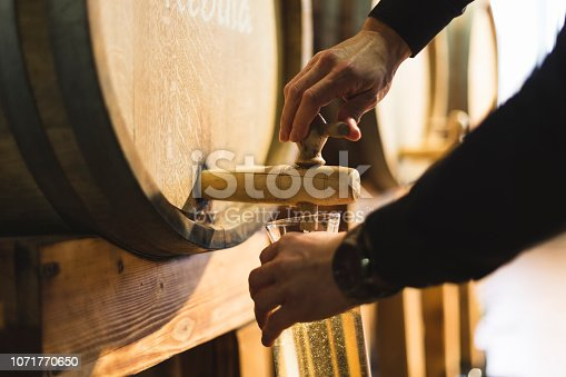 Close-up shot of man's hands pouring white wine into decanter.